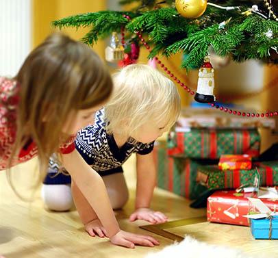 deux soeurs cherchant les cadeaux sous le sapin de noel