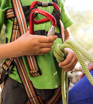 Enfant apprenant à utiliser les mousquetons de via ferrata en colo