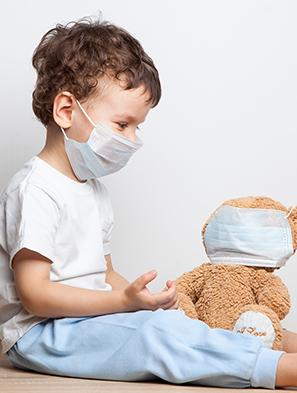 Enfant avec son nounours portant tous deux un masque de protection des virus