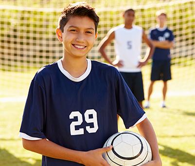 Ado jouant au football en colonie de vacances sportive cet été