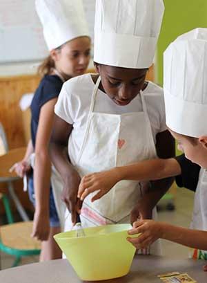Enfants cuisinant ensemble en colonie de vacances à la toussaint