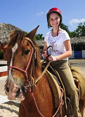 Jeune fille sur son cheval en colonie de vacances équitation à la toussaint