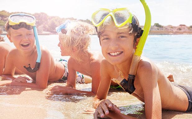 Groupe de jeunes enfants en bord de mer avec masque et tuba