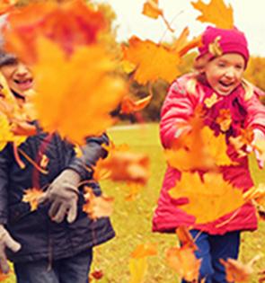 Enfants jouant avec les feuilles d'arbre de l'automne lors des colonies d'automne Djuringa