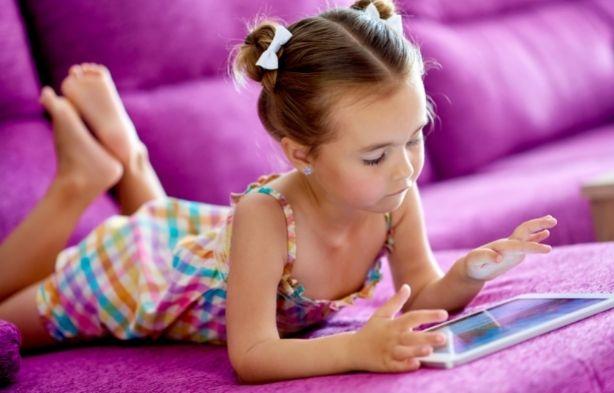 Fillette choisissant sa colo avec ses parents sur tablette