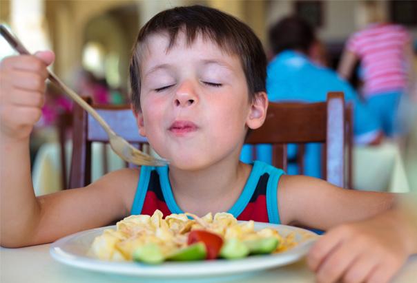 Enfant qui se régale avec les plats de la colo