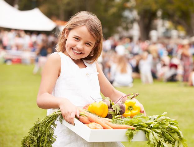 Jeune fille portant un panier de légumes bio