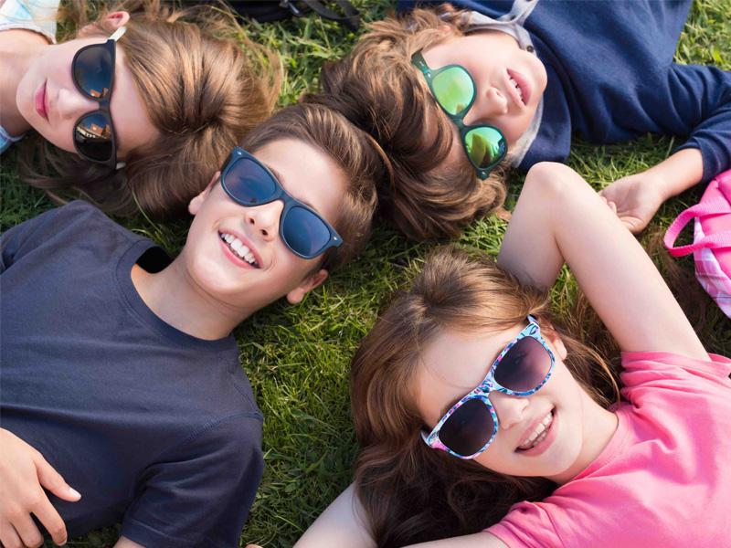 Enfants et ados dans l'herbe heureux, portant des lunettes de soleil