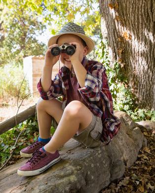 Petit garçon aventurier en train d'observer la nature à travers ses jumelles