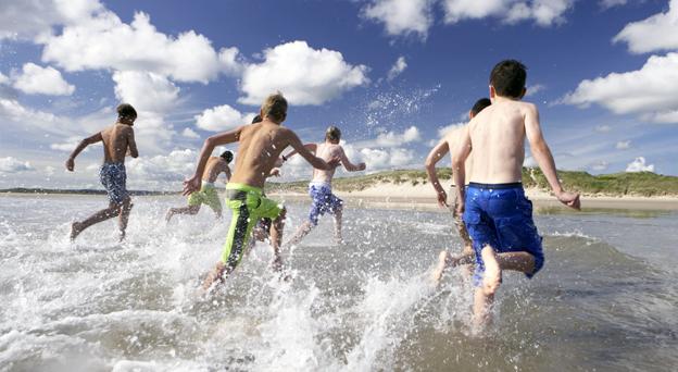 Groupe de pré-adolescents en train de courir dans la mer