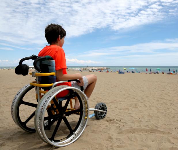 Enfant en situation de handicap moteur à la plage en colonie de vacances