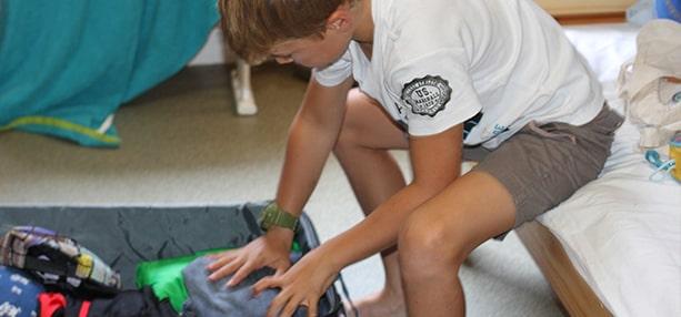 Garçon faisant sa valise en colonie de vacances