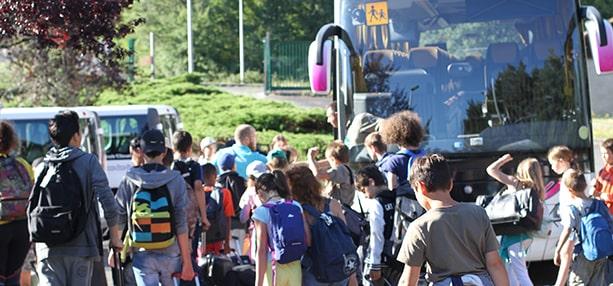Groupe d'enfants s'appretant à partir en colonie de vacances en bus