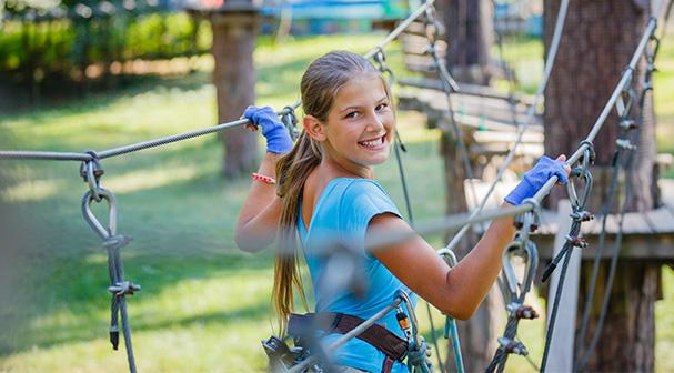 Jeune fille pratiquant l'accrobranche en colonie de vacances