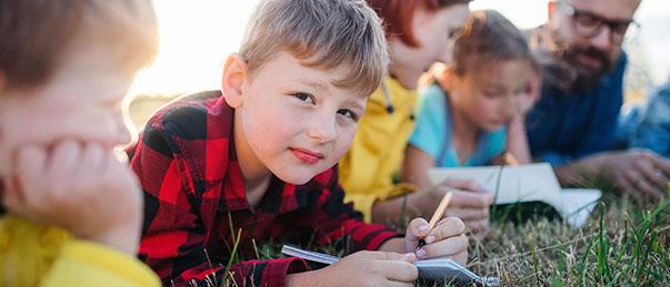Enfants en classe découverte prenant des notes dans l'herbe