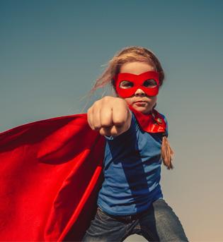 Jeune fille avec masque et cape de superheros