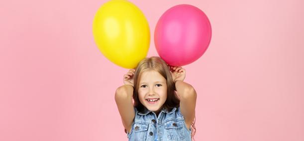 Fillette portant deux ballon de baudruche colorés en colonie de vacances
