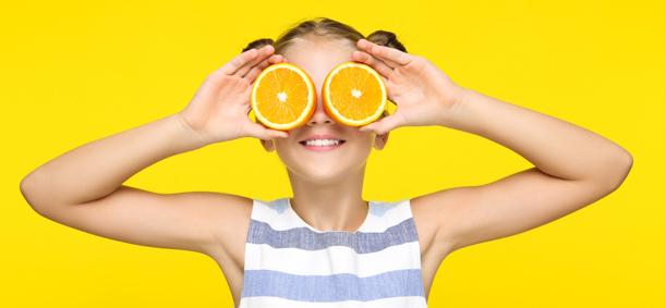 Fillette tenant deux ornages devant ses yeux heureuse de manger équilibré en colonie de vacances