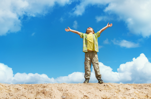 Enfant debout qui lève les bras au ciel