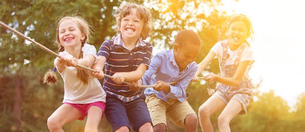 Enfants heureux qui s'amusent à tirer à la corde
