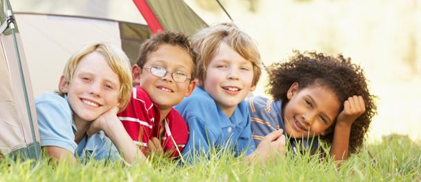 Plusieurs visages d'enfants sortant d'une tente
