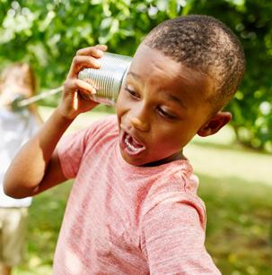 Jeune garçon qui écoute dans une boite de conserve