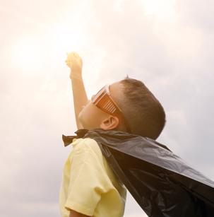 Jeune garçon avec une cape qui tend le bras vers le ciel tel un superhéros