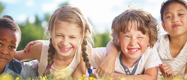 Enfants souriants qui s'amusent dans l'herbe