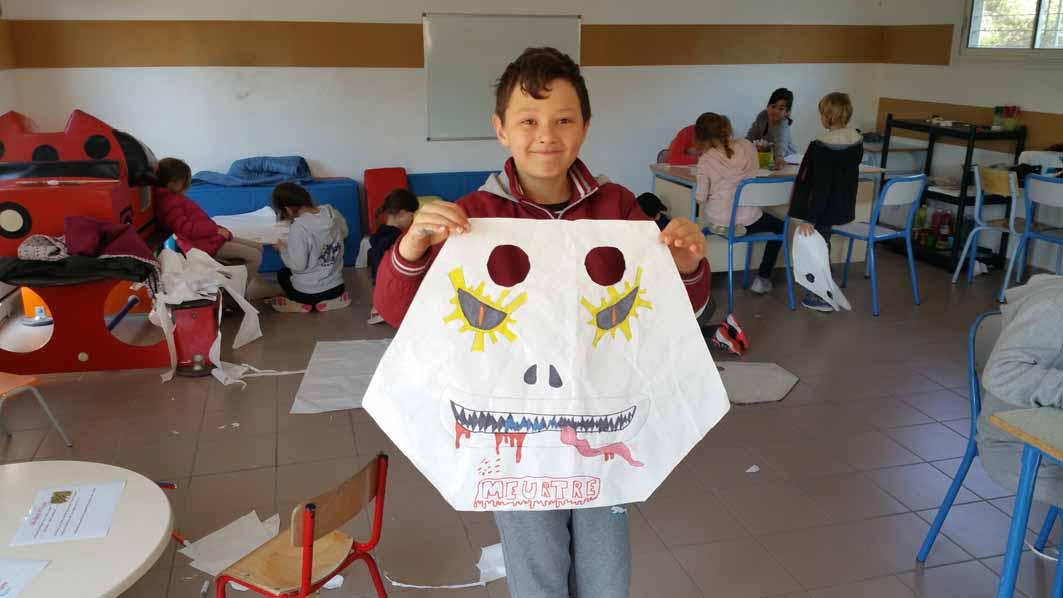 Enfant présentant sa création d'activité manuelle en colonie de vacances d'été