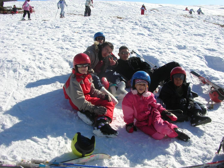 Groupe d'enfants assis dans la neige en colonie de vacances de février