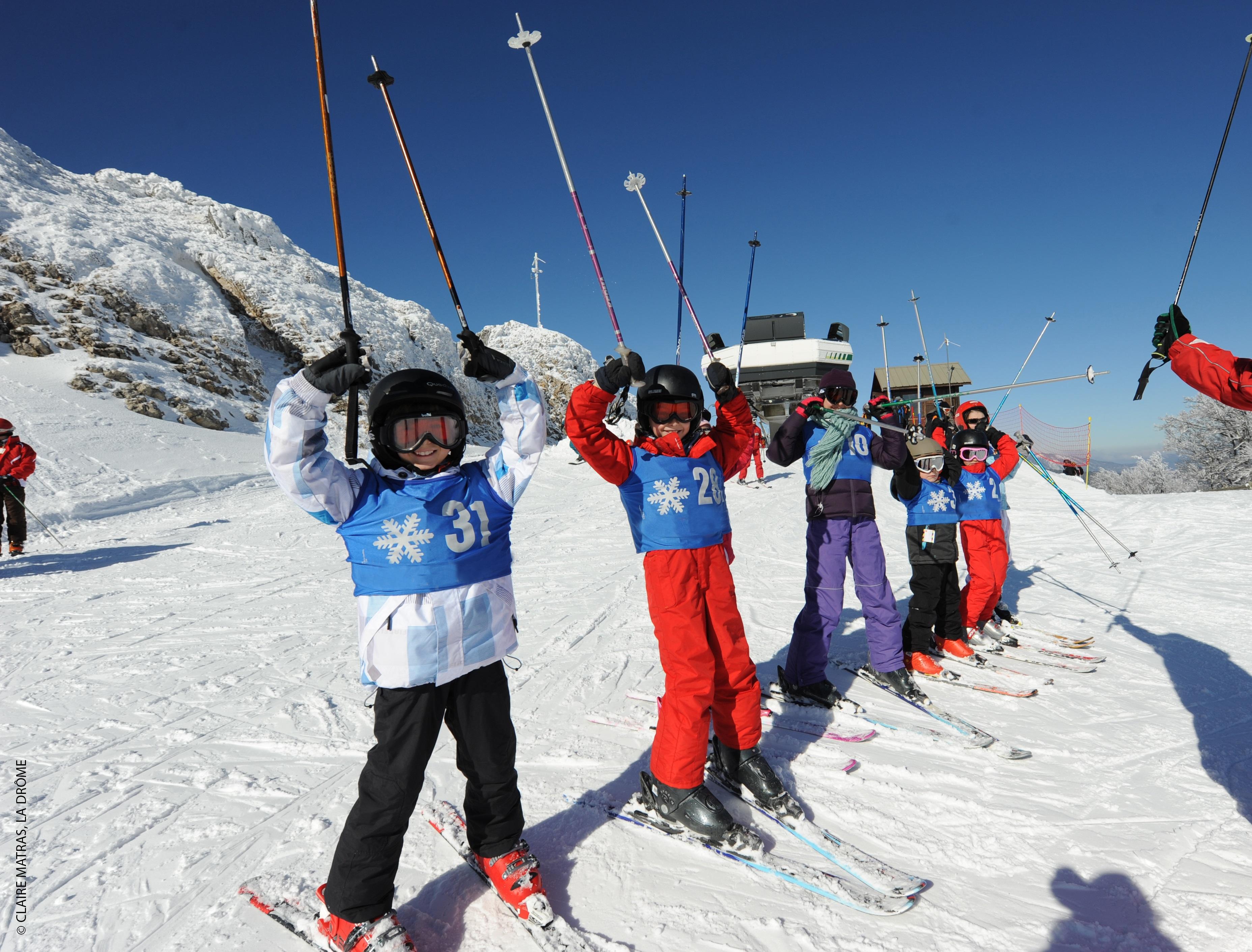 Groupe d'enfants heureux sur les pistes de ski en colonie de vacances