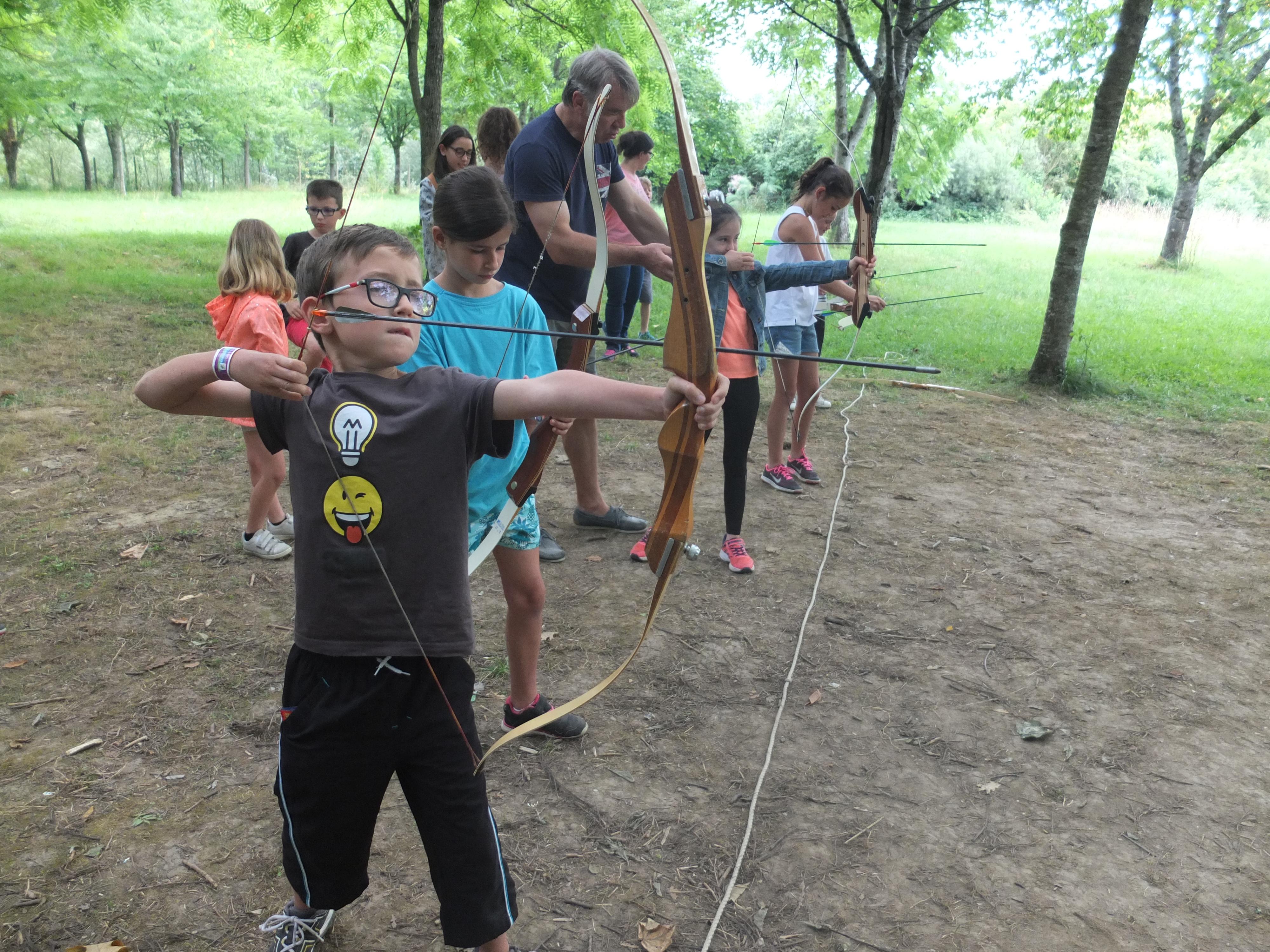 Enfants apprenant à faire du tir à l'arc en colonie de vacances d'été