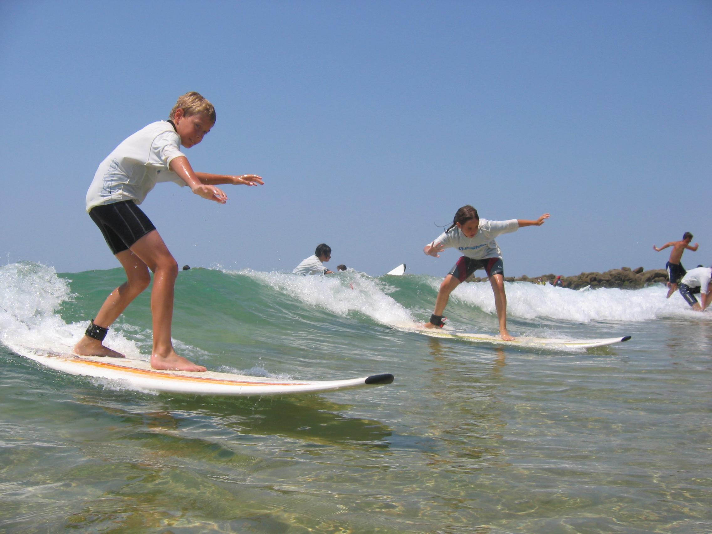 Enfant apprenant à faire du surf en colonie de vacances cet été