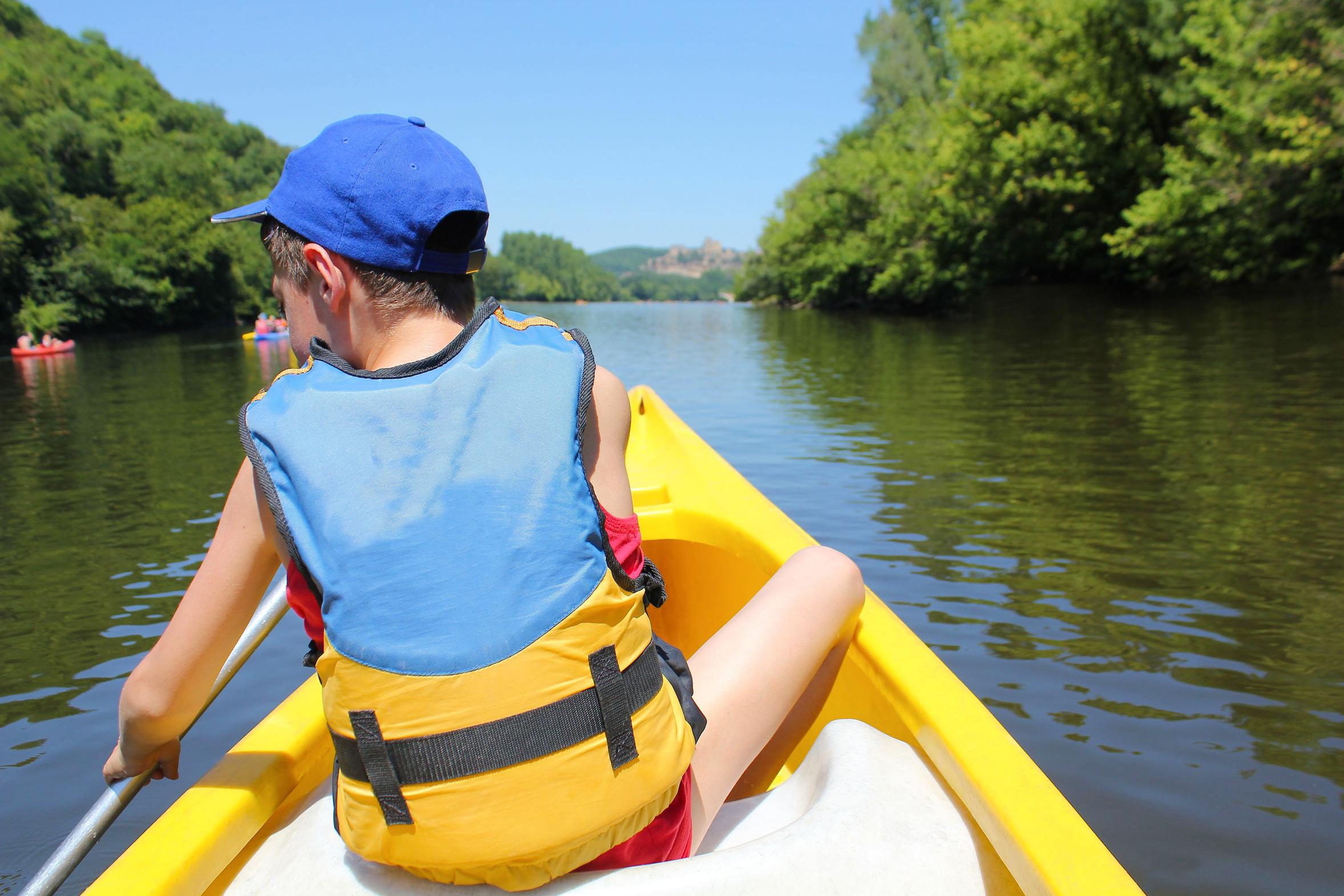 Enfant de dos sur un canoë en colonie de vacances