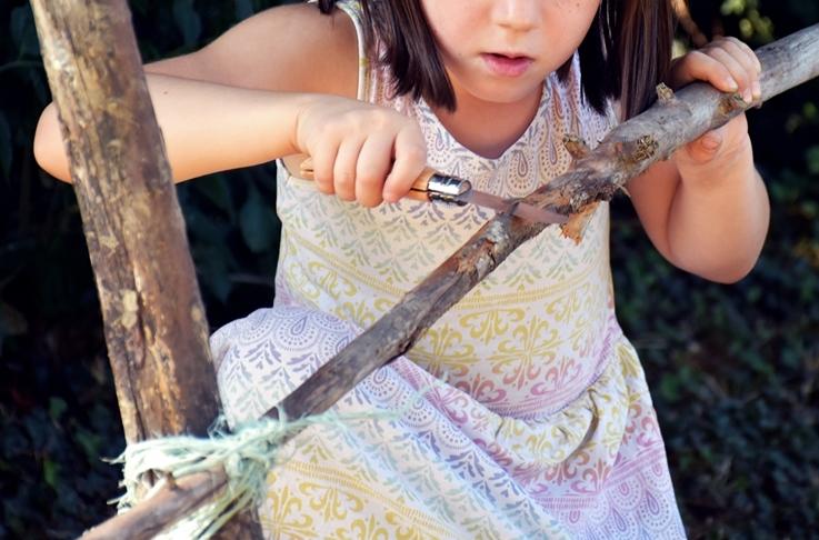Petite fille qui taille un bâton en colonie de vacances