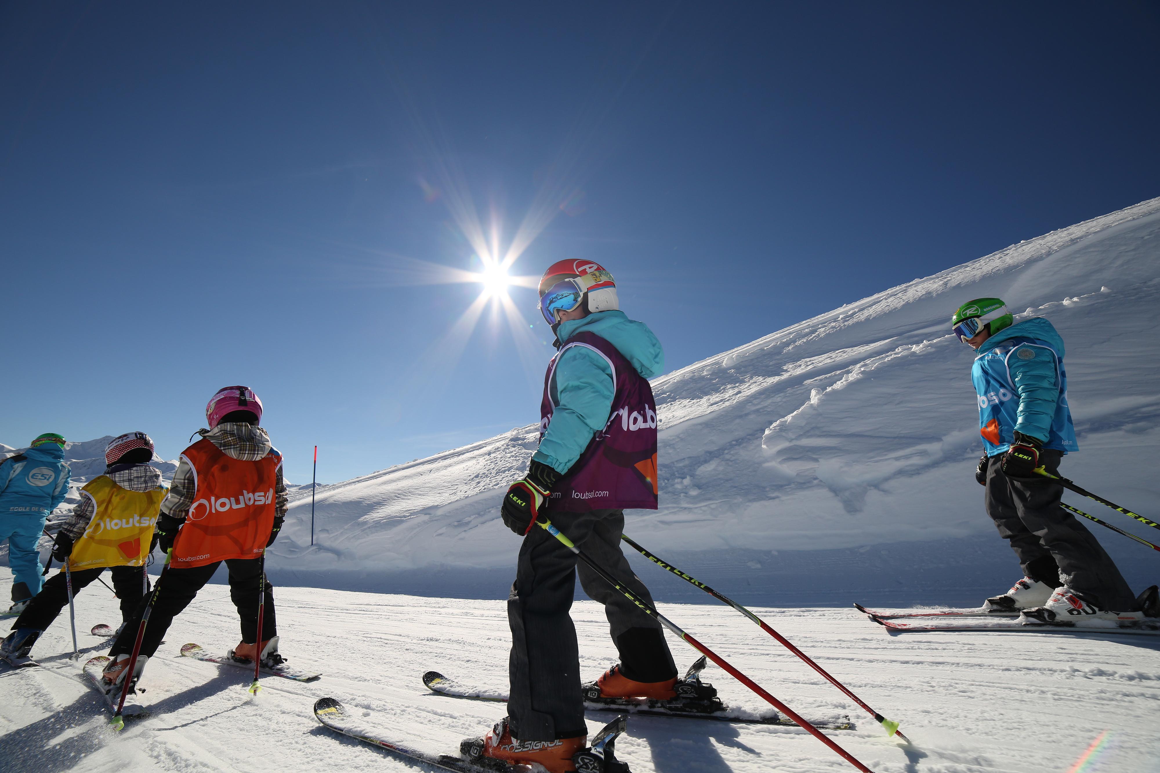Groupe d'enfants sur les pistes de ski en colonie de vacances à la montagne