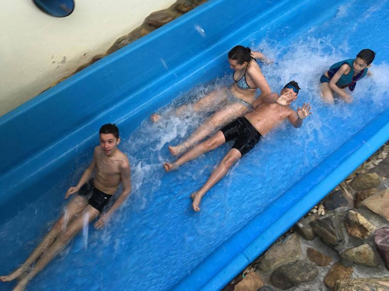 Enfants en colonie qui glissent dans un toboggan aquatique