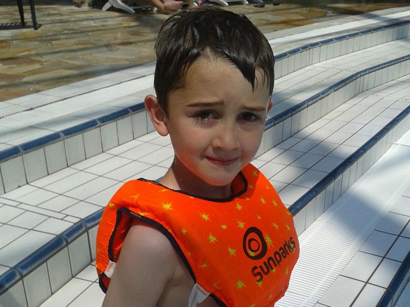Petit garçon dans la piscine avec des brassards