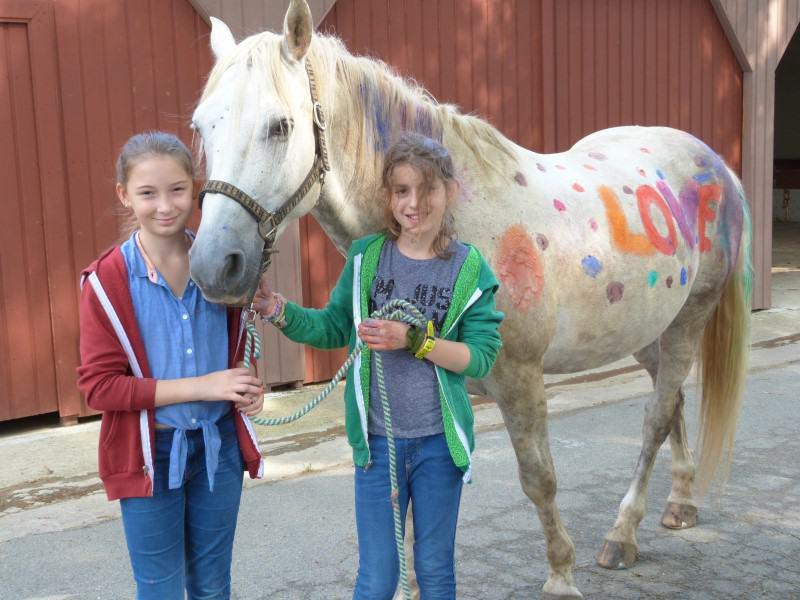 Portrait de fillettes en colonie de vacances avec leur cheval cet été