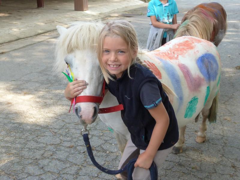 Portrait d'une fillette avec un cheval en colonie de vacances équitation cet été