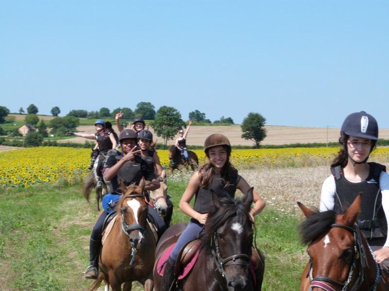 groupe d'enfants en balade à la compagne en colonie de vacances équitation cet été