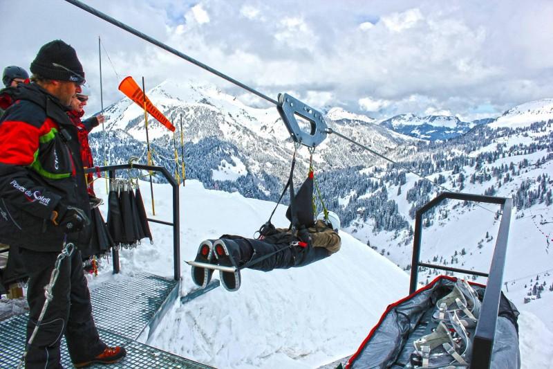 Enfants faisant de la tyrolienne au dessus des pistes de ski en colonie de vacances