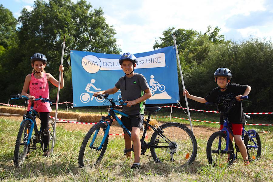 trois enfants au départ d'une course à vélo en colonie de vacances à la campagne