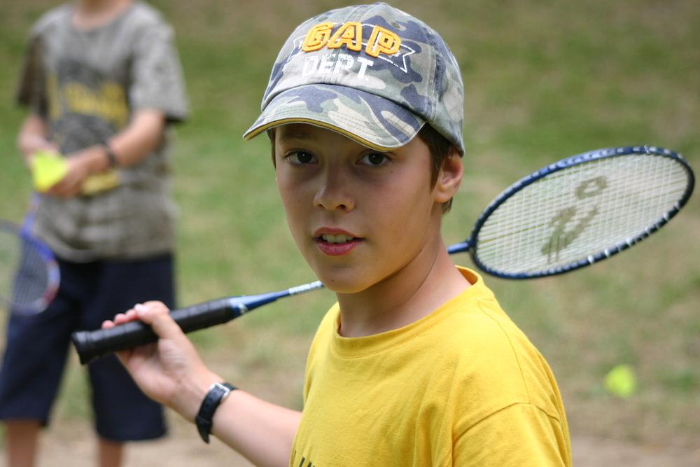 Portrait d'un jeune garçon faisant du tennis en colonie de vacances cet été