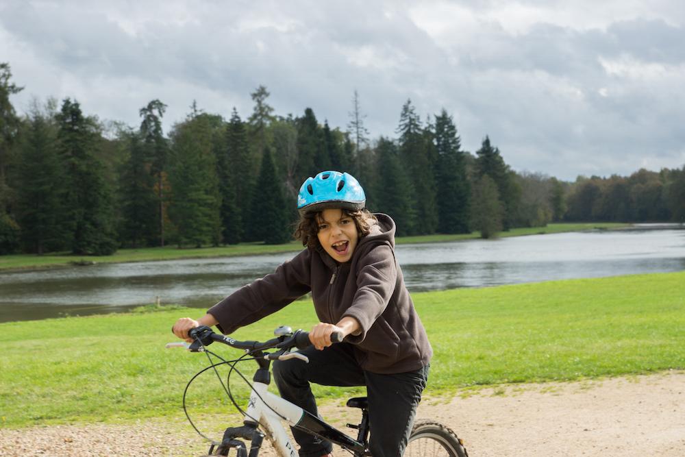 enfant faisant du vélo en colonie de vacances à la campagne cet été