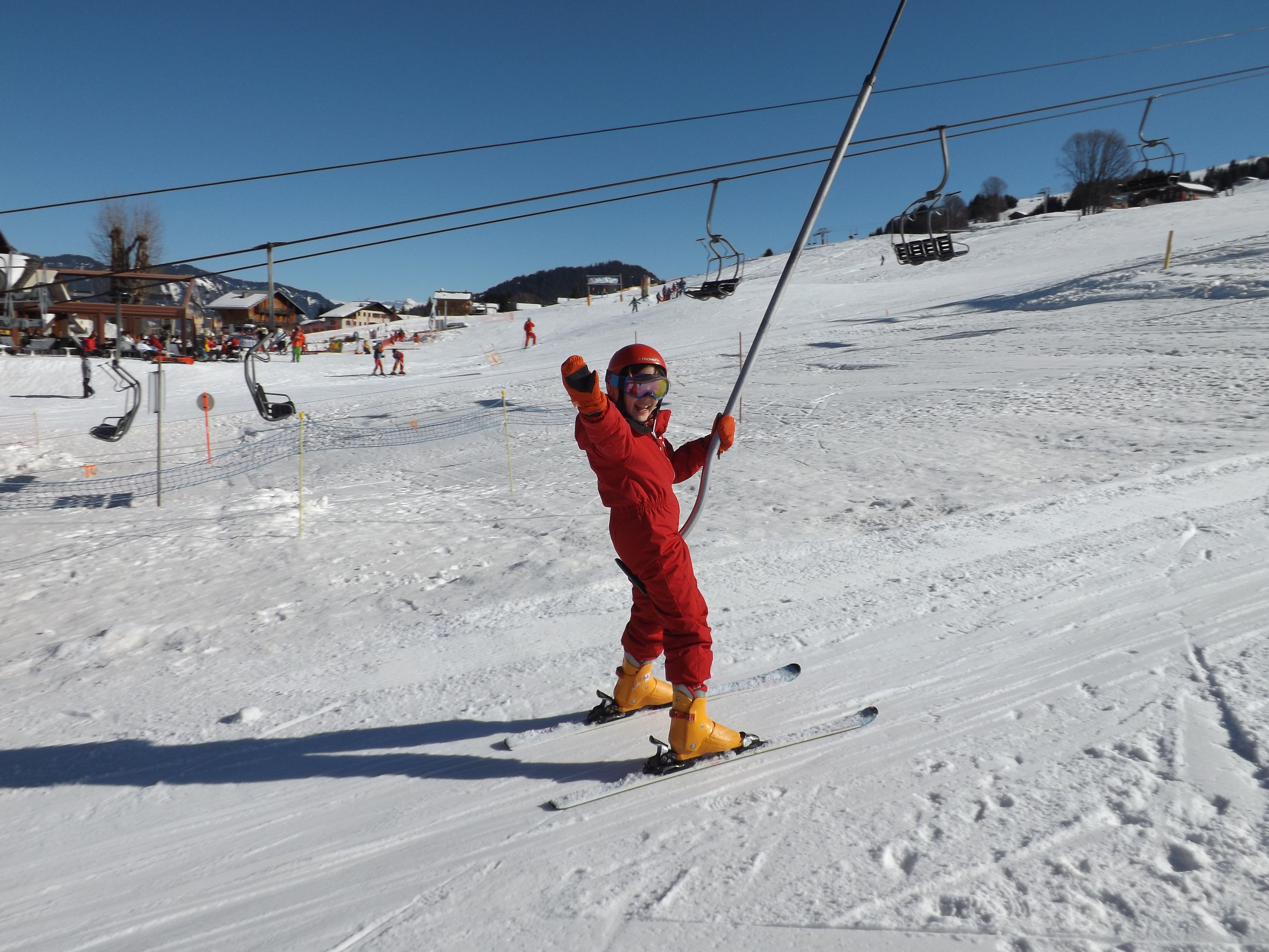 Enfant sur le tire fesse en colonie de vacances à la montagne en février