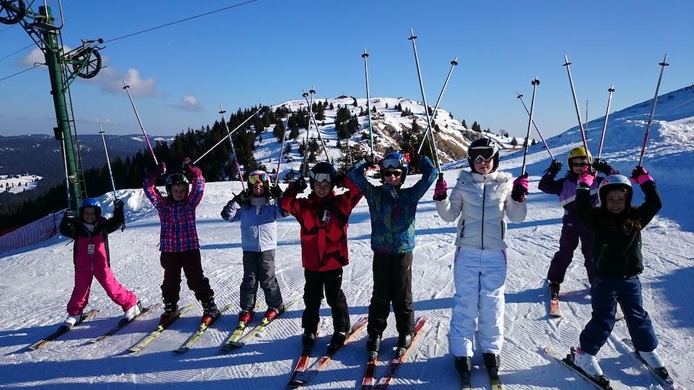 Groupe d'enfants sur les pistes de ski à la montagne en colonie de vacances