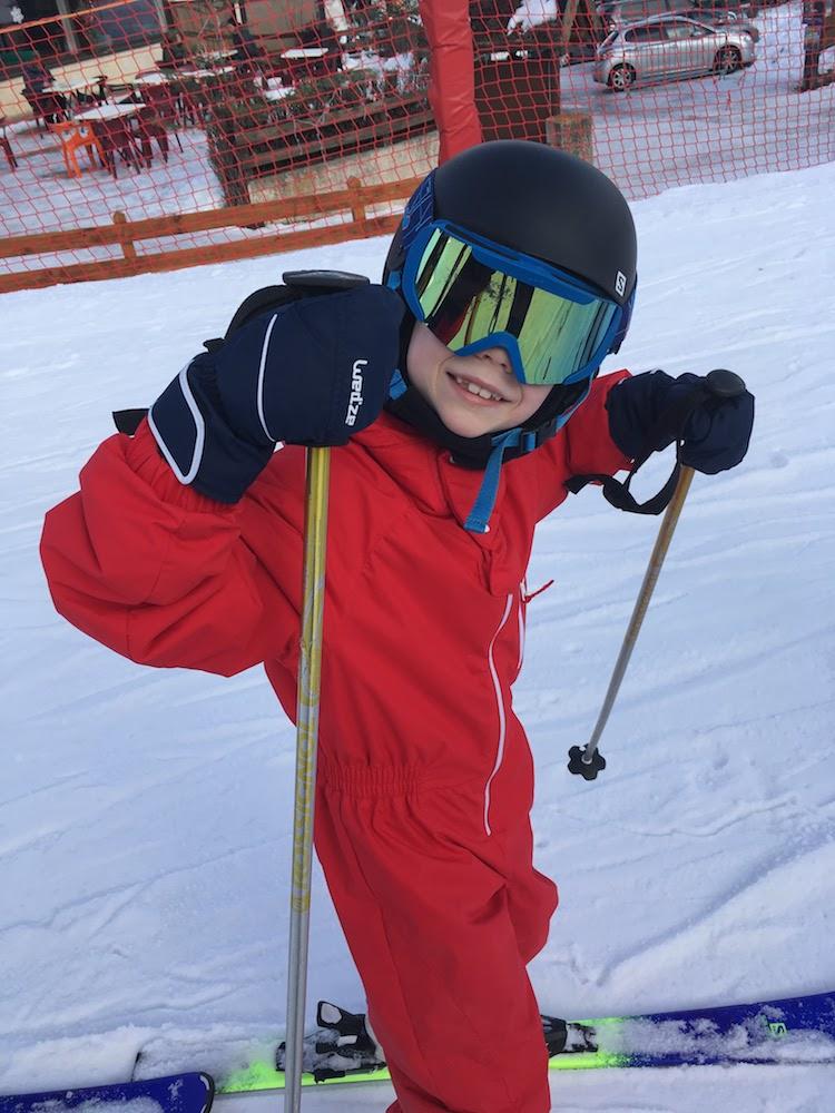 Enfant apprenant à skier en colonie de vacances à la montagne